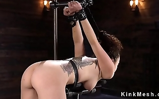 Slave bent over strapped with hair pulled back